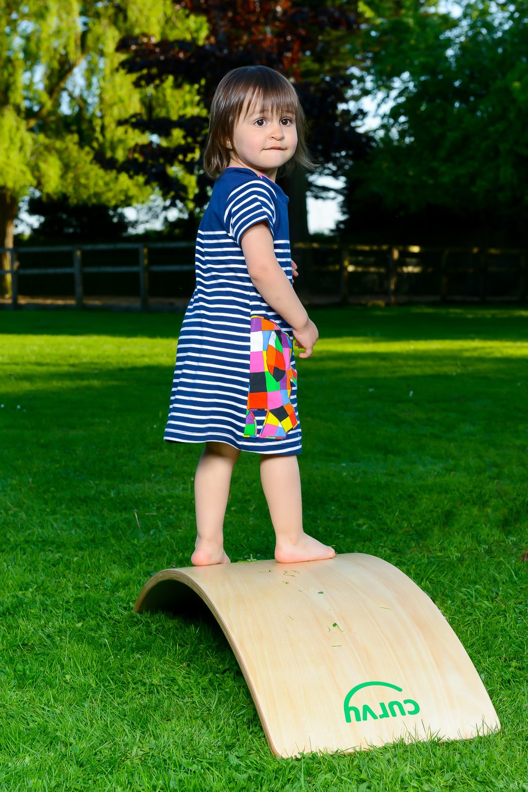 outdoors toddler standing on curvy balance board